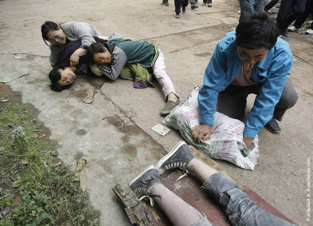 Relatives cry next to the recovered body of a student near a school at the earthquake-hit Hanwang Town of Mianzhu County, Sichuan province, May 14, 2008