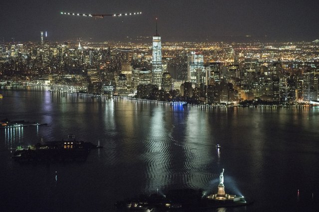 In this photo released by Jean Revillard/ SI2, solar-powered airplane Solar Impulse 2, piloted by Swiss adventurer Andre Borschberg, approaches Manhattan as it flies near the Statue of Liberty, foreground right, in New York Saturday, June 11, 2016, shortly before landing at John F. Kennedy International Airport. The solar-powered airplane on a globe-circling voyage that began more than a year ago in the United Arab Emirates reached a milestone Saturday, completing a trip across the United States with a Statue of Liberty fly-by before landing in New York. (Photo by Jean Revillard/SI2 via AP Photo)