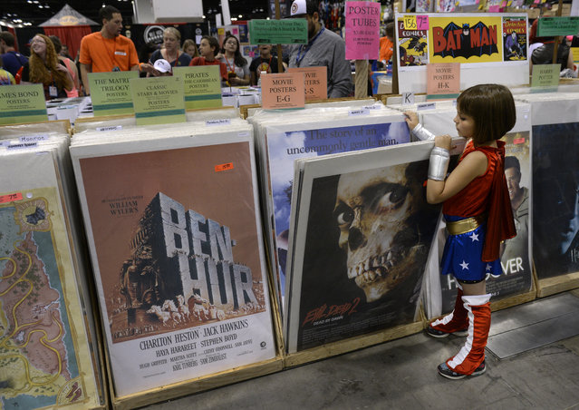 Brooke Hovet, 8, decided to dress as Wonder Woman today and spends time looking at some movie posters for sale. The Denver Comic Con and Literacy Conference takes place at the Colorado Convention Center from June 13-15, 2014. The three-day pop culture convention features comics along with sci-fi and fantasy TV shows, movies, Japanese Animation, cosplay, toys, gaming and panel presentations. Celebrities and artists from film and television will also make appearances. (Photo by Kathryn Scott Osler/The Denver Post)