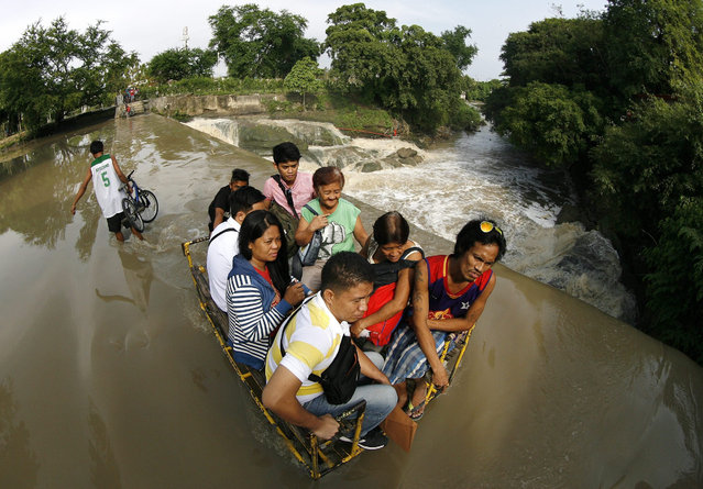Filipino villagers ride on a makeshift cart to cross a swelling river in Las Pinas city, south of Manila, Philippines, 06 August 2015. At least seven people were killed and three are missing as flashfloods swept through villages in the southern Philippines, an official of the regional Office of Civil Defense said. An official said that hundreds of families were displaced by the floods that hit villages in Valencia town and Malaybalay City in Bukidnon province. (Photo by Francis R. Malasig/EPA)