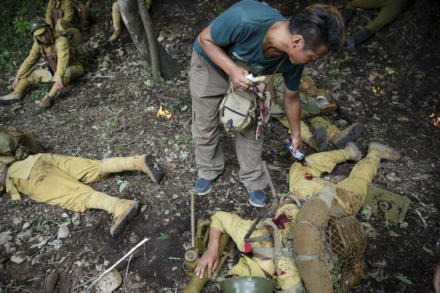 """A crew member applies fake blood to the clothes of actors playing dead and wounded Japanese soldiers during filming of """"The Last Prince"""" television series on location near Hengdian World Studios near Hengdian July 24, 2015. (Photo by Damir Sagolj/Reuters)"""