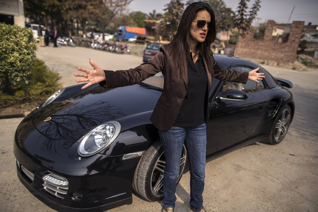 Ansa Hasan, a marketing manager at Porsche Pakistan, gestures as she prepares for an upcoming event, outside the Porsche showroom in Lahore February 21, 2014. (Photo by Zohra Bensemra/Reuters)