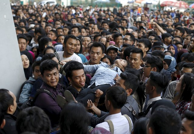 Job seekers carry a woman who fainted at the Indonesia Spectacular Job Fair 2015 at Gelora Bung Karno stadium in Jakarta August 12, 2015. Indonesia's gross domestic product grew at 4.67 percent in the second quarter, its slowest pace in six years. Since he took office last October, Widodo's government has passed a raft of measures aimed at boosting industry and consumption that have been criticized by investors as protectionist. (Photo by Reuters/Beawiharta)