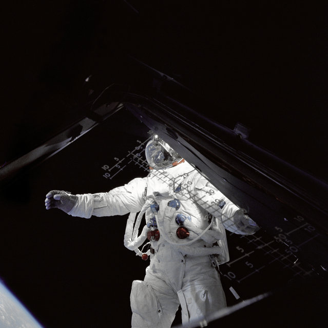 "Astronaut Russell L. Schweickart, Lunar Module pilot, stands in ""golden slippers"" on the Lunar Module ""Spider's"" porch during his extravehicular activity on the fourth day of the Apollo 9 earth-orbital mission. This photograph was taken from inside the Lunar Module ""Spider"". The Command/Service Module and Lunar Module were docked. Schweickart is wearing an Extravehicular Mobility Unit (EMU). (Photo by NASA)"