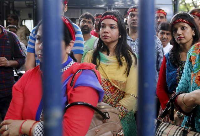 """Supporters of Radhe Ma, a self styled """"god woman"""" wait outside a police station in Mumbai, India, August 14, 2015. A trident-toting Indian """"god woman"""" worshipped as a miracle worker was questioned by police on Friday over accusations that she tried to extort dowry money from brides, the latest in a long line of popular gurus to run into legal problems. (Photo by Shailesh Andrade/Reuters)"""