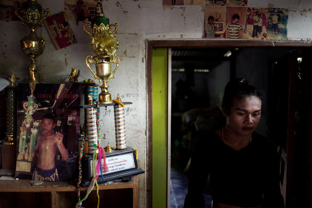 Muay Thai boxer Nong Rose Baan Charoensuk, 21, who is transgender, walks next to her trophies at her house in Phimai district in Nakhon Ratchasima province, Thailand, July 18, 2017. (Photo by Athit Perawongmetha/Reuters)