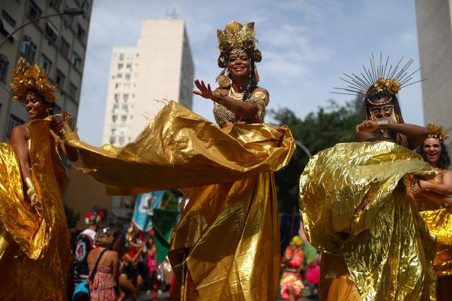 "Revellers in shiny gold outfits perform at the annual block party known as ""Cordao de Boitata"", during Carnival festivities in Rio de Janeiro, Brazil February 16, 2020. (Photo by Pilar Olivares/Reuters)"