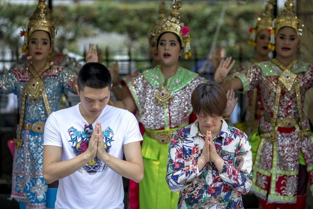 People pray as Thai classical dancers perform at the Erawan shrine, the site of Monday's deadly blast, in central Bangkok, Thailand, August 21, 2015. Thai government officials and police chiefs attended a religious ceremony on Friday for the victims of the country's worst ever bombing but appeared no closer to determining who carried out the attack and why. (Photo by Athit Perawongmetha/Reuters)