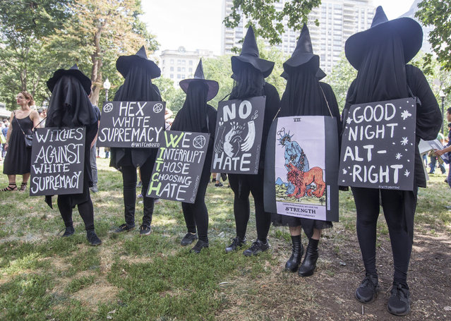 "Counter protesters in witch costumes hold up signs after a march to the ""Free Speech Rally"" on Boston Common on August 19, 2017 in Boston, Massachusetts. Thousands of demonstrators and counter-protestors are expected at Boston Common where the Boston Free Speech Rally is being held. (Photo by Scott Eisen/Getty Images)"