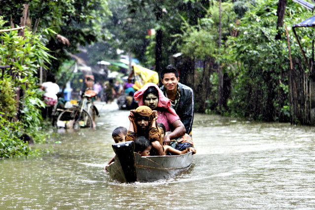 Local residents ride a boat on a flooded road overflown by the Bago river at a low-lying part in Bago, 80 kilometers (50 miles) northeast of Yangon, Myanmar, Monday, August 4, 2014. Flooding is common during Myanmar's monsoon season, which typically starts in late May and ends in mid-October. (Photo by Khin Maung Win/AP Photo)