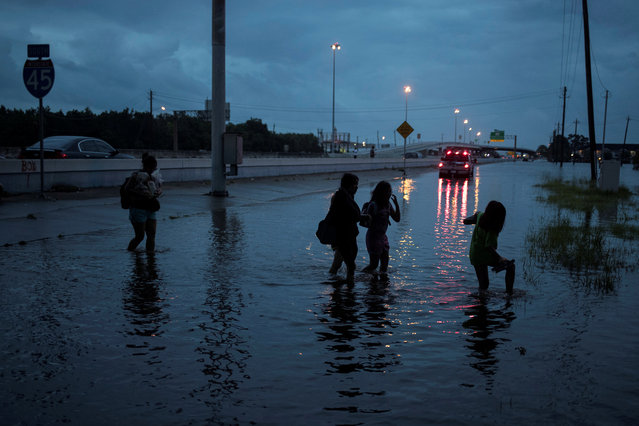 Members of the Duong family walk through flood waters on the feeder road of Interstate 45 in Houston, Texas on August 28, 2017. (Photo by Adrees Latif/Reuters)