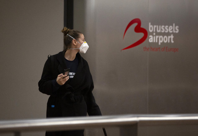 A woman wears a protective mask as she arrives at Brussels International Airport in Brussels, Friday, March 13, 2020. European Union interior ministers on Friday were trying to coordinate their response to the COVID-19 coronavirus as the number of cases spreads throughout the 27-nation bloc and countries take individual measures to slow the disease down. For most people, the new coronavirus causes only mild or moderate symptoms, such as fever and cough. For some, especially older adults and people with existing health problems, it can cause more severe illness, including pneumonia. (Photo by Virginia Mayo/AP Photo)