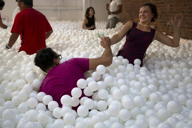 "People play in the ""JumpIn!"" ball pit, an interactive art installation by creative agency Pearlfisher made up of 81,000 white balls, in New York City August 25, 2015. (Photo by Mike Segar/Reuters)"