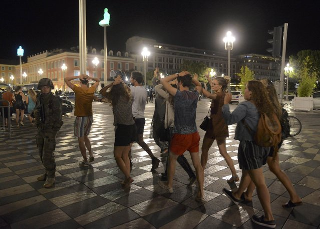 People cross the street with their hands on thier heads as a French soldier secures the area July 15, 2016 after at least 60 people were killed along the Promenade des Anglais in Nice, France, when a truck ran into a crowd celebrating the Bastille Day national holiday July 14. (Photo by Jean-Pierre Amet/Reuters)