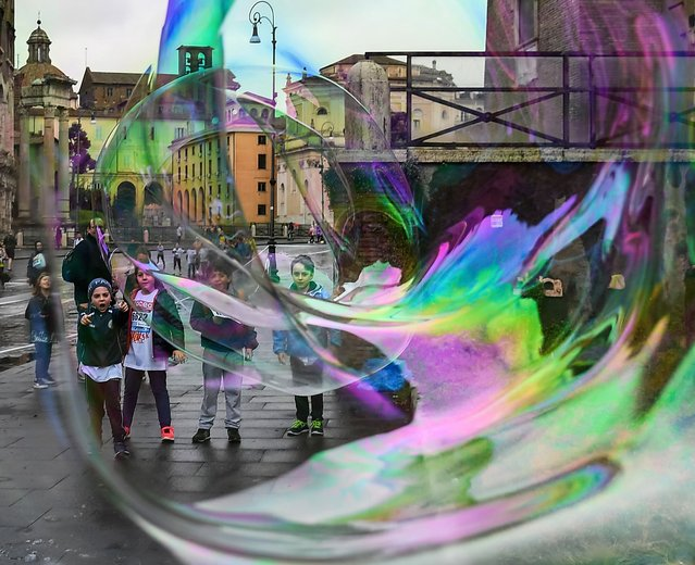 Children play with giant soap bubbles blown by a man for tourists and children on April 7, 2019 in Rome. (Photo by Vincenzo Pinto/AFP Photo)