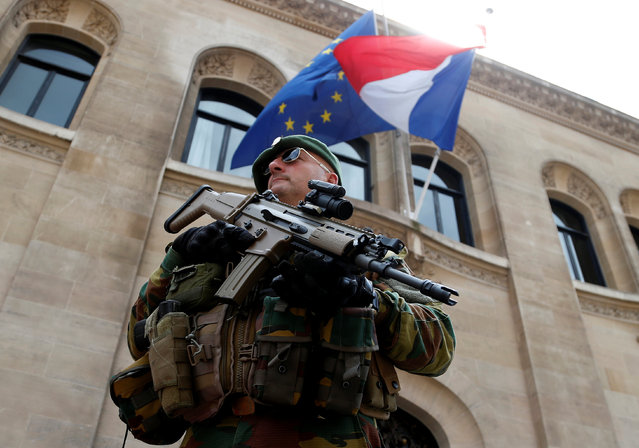 A Belgian soldier stands guard in front of the French embassy as French and European Union flags flutter at half staff to honor the victims of the Bastille Day truck attack in Nice, in Brussels, Belgium, July 15, 2016. (Photo by Francois Lenoir/Reuters)