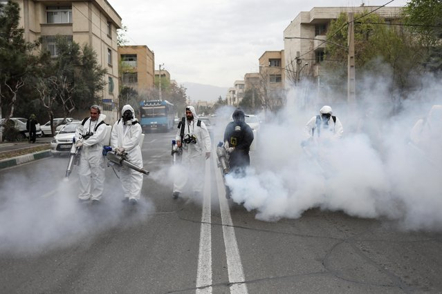 Firefighters wear protective face masks as they disinfect the streets ahead of the Iranian New Year Nowruz in Tehran, Iran, March 18, 2020. (Photo by Ali Khara/WANA via Reuters)