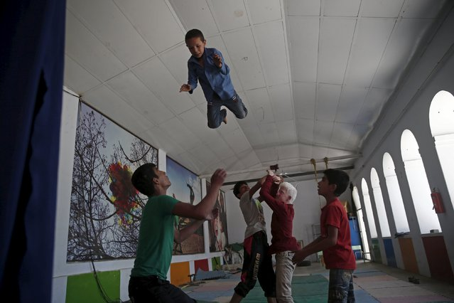 Boys who are part of Afghan Mobile Mini Circus for Children (MMCC), practise their acrobatic skills in Kabul, Afghanistan August 17, 2015. The MMCC, founded by David Mason from Denmark, teaches cooperation and creativity to children scarred by years of war in Afghanistan. Despite the dangers, the project has grown so popular that it now runs centres in ten provinces and has hundreds of regular students. (Photo by Ahmad Masood/Reuters)