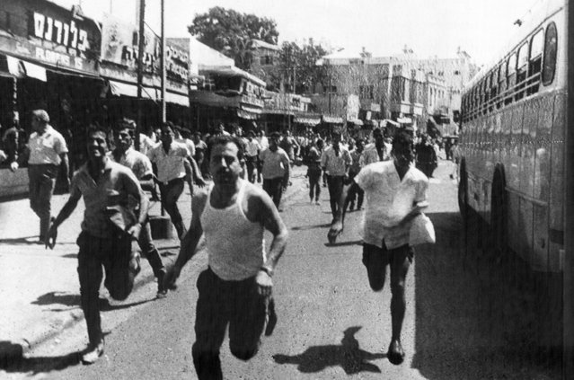 Israelis scatter in Tel Aviv, September 4, 1968 after three terrorist bombs exploded in a crowded bus station, killing one man and injuring 49 others. The bombs, hidden in litter bins, sent pieces of metal flying like shrapnel into crowds of waiting Israeli and Arab passengers. It was the worst incident of sabotage in Tel Aviv in ten years. (Photo by AP Photo)