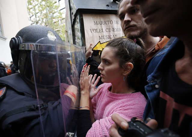 Spanish police push people with a shield outside a polling station in Barcelona, on October 1, 2017, on the day of a referendum on independence for Catalonia banned by Madrid. More than 5.3 million Catalans are called today to vote in a referendum on independence, surrounded by uncertainty over the intention of Spanish institutions to prevent this plebiscite banned by justice. (Photo by Pau Barrena/AFP Photo)