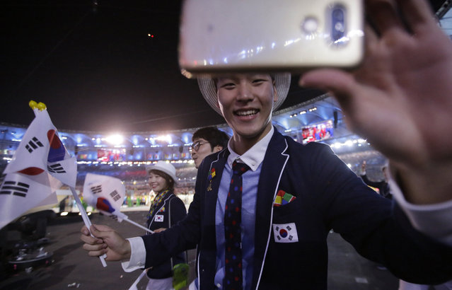 A member of the South Korean team holds up his phone as he marches in the arena during the opening ceremony for the 2016 Summer Olympics in Rio de Janeiro, Brazil, Friday, August 5, 2016. (Photo by David Goldman/AP Photo)