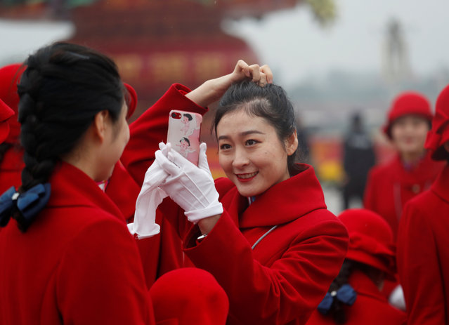 Ushers prepare themselves for photos at the Tiananmen Square during the opening of the 19th National Congress of the Communist Party of China at the Great Hall of the People in Beijing, China on October 18, 2017. (Photo by Ahmad Masood/Reuters)