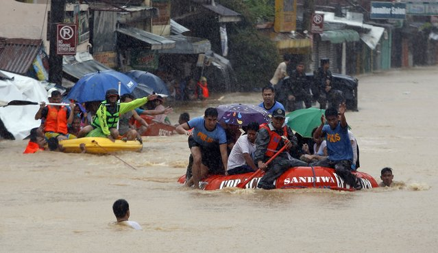 People are evacuated on rescue boats after their homes were swamped by heavy flooding in Marikina, metro Manila, September 19, 2014. (Photo by Erik De Castro/Reuters)