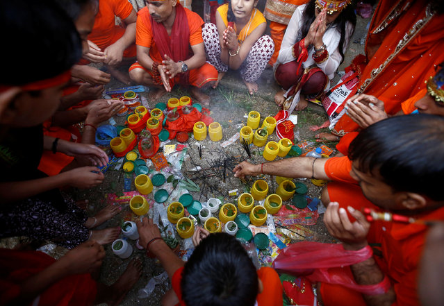 "Devotees perform ritual gathering around the holy water collected in plastic bottles from the Bagmati River as they take part in the ""Bol Bom"" (Say Shiva) pilgrimage in Kathmandu, Nepal, August 8, 2016. The faithful, chanting the name of Lord Shiva, run about 15 km (9 miles) barefooted toward Pashupatinath temple seeking good health, wealth and happiness. (Photo by Navesh Chitrakar/Reuters)"