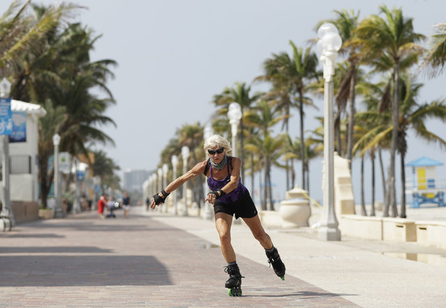 A rollerblader skates on the Broadwalk on Hollywood beach, Tuesday, May 19, 2020, in Hollywood, Fla. Broward County started a phased reopening Monday. (Photo by Wilfredo Lee/AP Photo)