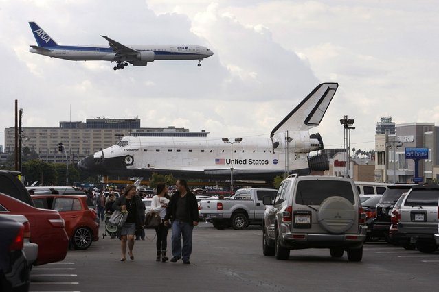 A jet lands at Los Angeles International Airport (LAX) behind the space shuttle Endeavour during a break in its movement as it is transported from LAX to the California Science Center in Exposition Park where it will be on permanent public display on October 12, 2012 in Los Angeles, California. Endeavour was flown cross-country atop NASA's Shuttle Carrier Aircraft from Kennedy Space Center in Florida to LAX on its last flight ever on September 21. Completed in 1991, Endeavour was built to replace the space shuttle Challenger which disintegrated during a catastrophic re-entry accident. This fifth and final space shuttle orbiter circled the earth 4,671 times and traveled nearly 123 million miles during its 25 missions from 1992 to 2011. (Photo by David McNew)
