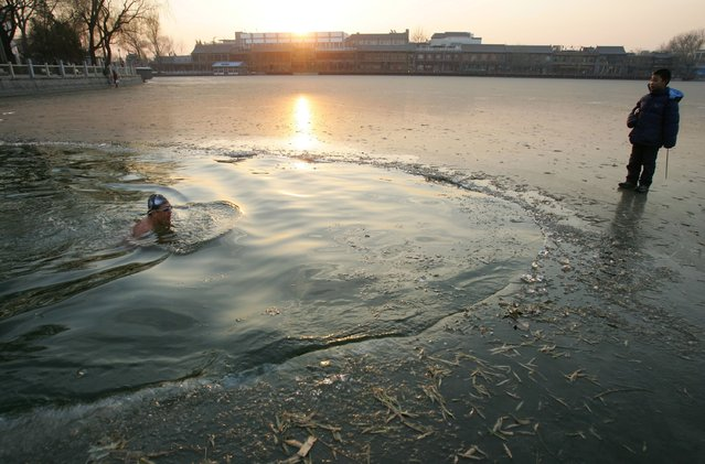A man swims in the icy Shichahai Lake as a child looks on at a temperature around zero degrees centigrade December 17, 2006 in Beijing, China. Shichahai Lake is a popular place for swim enthusiasts in Beijing to go winter swimming. (Photo by China Photos)