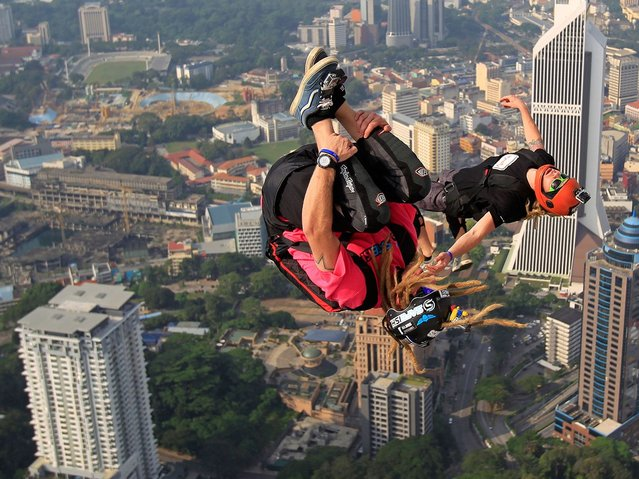 Britain's BASE jumper Sam Hardy lives up to his name after throwing himself off the top of the 335m-high Kuala Lumpur Tower during the KL Tower International Jump in Kuala Lumpur, Malaysia, Saturday, September 27, 2014. BASE stands for the places such jumpers usually jump from: buildings, antennas, spans (bridges) and earth (cliffs). (Photo by Lai Seng Sin/AP Photo)