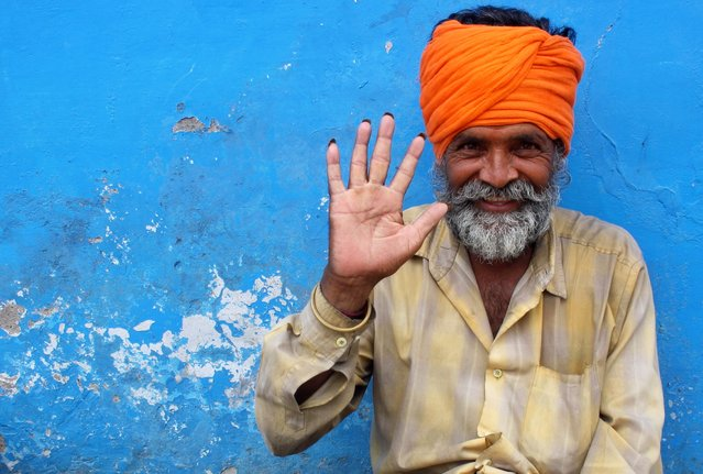 """""""Namaste"""". A group of holy men were scattered along the sides of a quiet street relaxing in the warm afternoon sun in the beautiful desert town of Pushkar, Rajasthan. The vibrant orange of this particular man's traditional Pagri head piece contrasted beautifully with the chipped blue wall behind him. Photo location: Pushkar, Rajasthan State, India. (Photo and caption by Angela Winter/National Geographic Photo Contest)"""