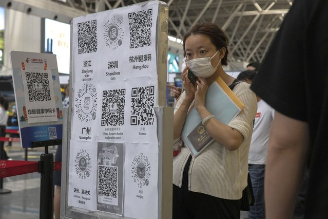 A passenger looks at a board with QR codes for health screening from different provinces at the Beijing Capital Airport terminal 2 in Beijing on Wednesday, June 17, 2020. The Chinese capital on Wednesday canceled more than 60% of commercial flights and raised the alert level amid a new coronavirus outbreak, state-run media reported. (Photo by Ng Han Guan/AP Photo)