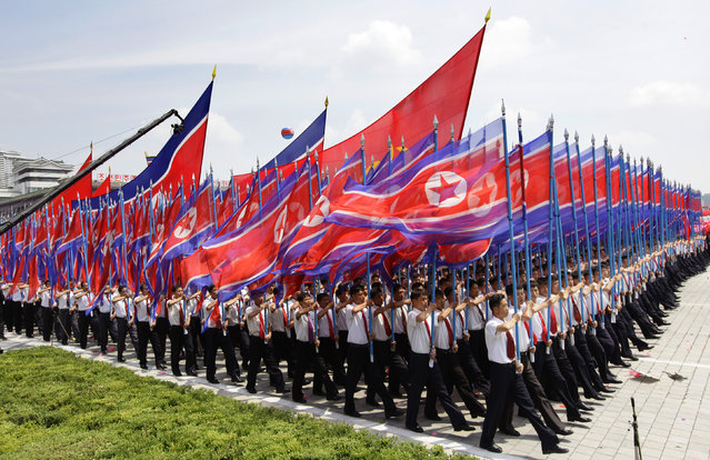 North Koreans holding national flags march during a parade to mark the 60th anniversary of the signing of a truce in the 1950-1953 Korean War at Kim Il-sung Square, in Pyongyang, July 27, 2013. (Photo by Jason Lee/Reuters)