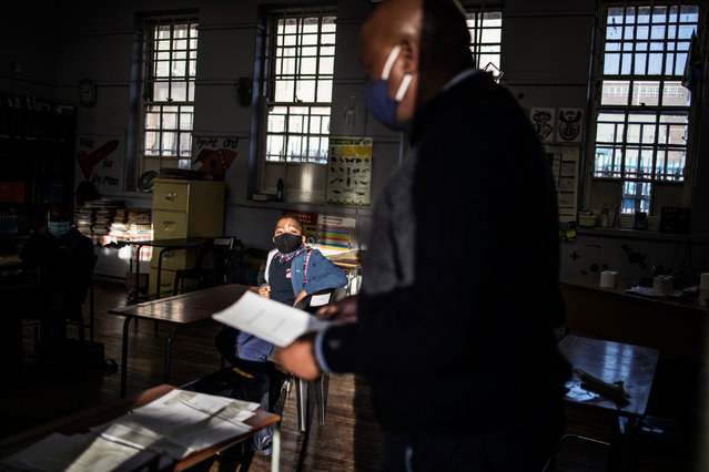 Pupils at the City Kidz Pre & Primary School in the Inner City district in Johannesburg sits in class as a teacher checks the register on June 1, 2020. South Africa moved into level three of a five-tier lockdown on June 1, 2020, to continue efforts to curb the spread of the COVID-19 coronavirus. Under level three, all but high-risk sectors of the economy will be allowed to reopen There are however a lot of confusion around the reopening of schools as some schools have opened and others remain closed. (Photo by Marco Longari/AFP Photo)
