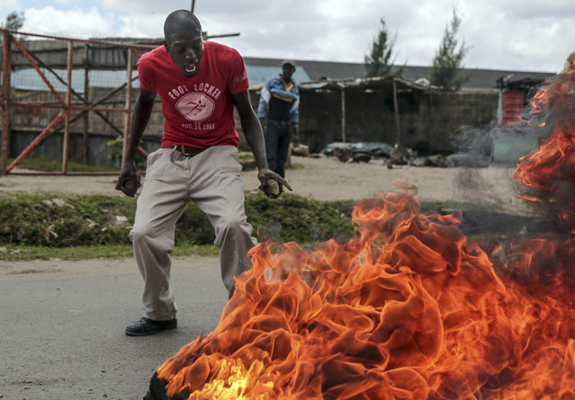 An opposition supporter reacts at a barricade during clashes with police in the Jacaranda grounds quarter in Nairobi, Kenya, Tuesday, November 28, 2017. As Kenyan President Uhuru Kenyatta was sworn in for a second term in front of tens of thousands who gathered to celebrate what they hoped would be the end of months of election turmoil, police fired guns and tear gas in other parts of the capital to stop the opposition from holding demonstrations to mourn dozens killed by police and militia since August. (Photo by Brian Inganga/AP Photo)