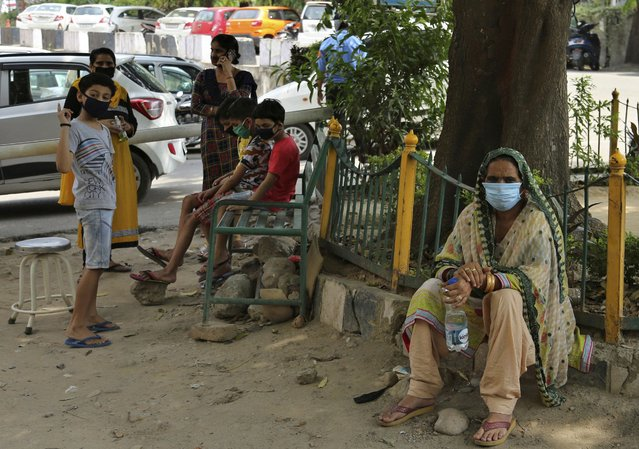 Indians wearing face masks wait to consult doctors outside a COVID-19 screening facility at a government run hospital in Jammu, Saturday, June 27, 2020. India is the fourth hardest-hit country by the pandemic in the world after the U.S., Russia and Brazil. (Photo by Channi Anand/AP Photo)
