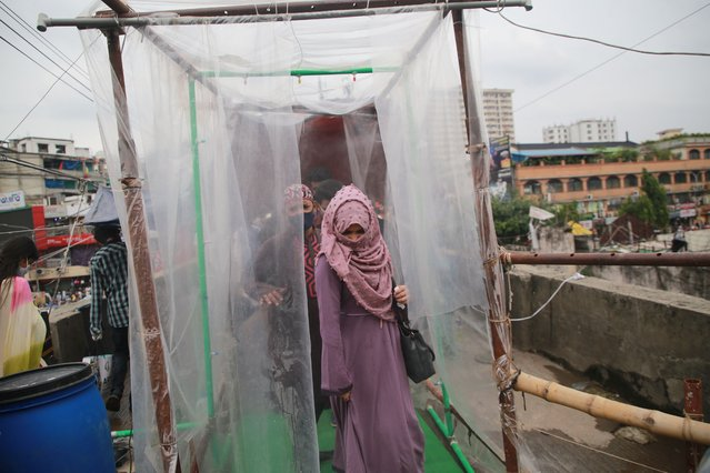 People going through a disinfection chamber in front of a shopping Mall to buy clothes ahead of the Eid-Al-Fitr festival which is marks end of the Islamic holy month of Ramadan, during a lockdown following the COVID-19 coronavirus outbreak in Dhaka, Bangladesh on May 22, 2020. (Photo by Rehman Asad/NurPhoto via Getty Images)