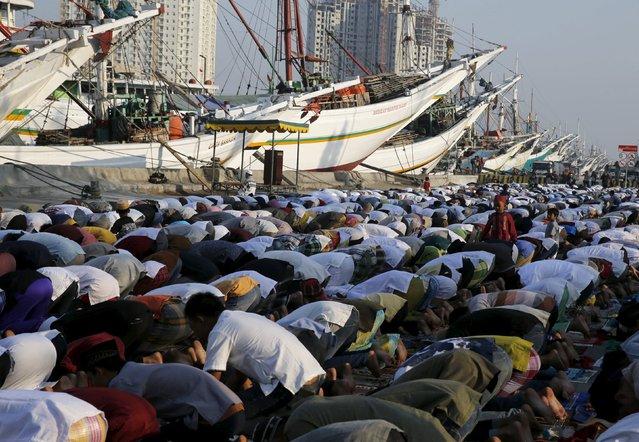 People pray near wooden boats during an Eid al-Adha mass prayer at Sunda Kelapa port in Jakarta September 24, 2015. (Photo by Reuters/Beawiharta)