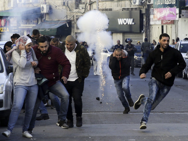 Palestinians run away from a sound bomb during clashes with Israeli security forces following a protest against U.S. President Donald Trump's decision to recognize Jerusalem as the capital of Israel in Jerusalem, Saturday, December 9, 2017. (Photo by Mahmoud Illean/AP Photo)