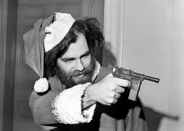 "Yippie leader Jerry Rubin, barred on December 4, from House Un-American Activities subcommittee hearing, aims a toy gun in ""self defense"" outside the Washington hearing room on December 5, 1969. Rubin showed up in his Santa Clause suit because he believed it was typical of the committee which, he said, ""is a total circus"". (Photo by Bob Daugherty/AP Photo)"