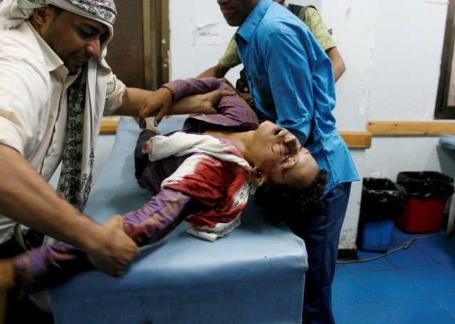 Volunteers help a youth injured by a shell during fighting between pro-government militants and Houthi militia men in Yemen's southwestern city of Taiz September 29, 2015. (Photo by Reuters/Stringer)