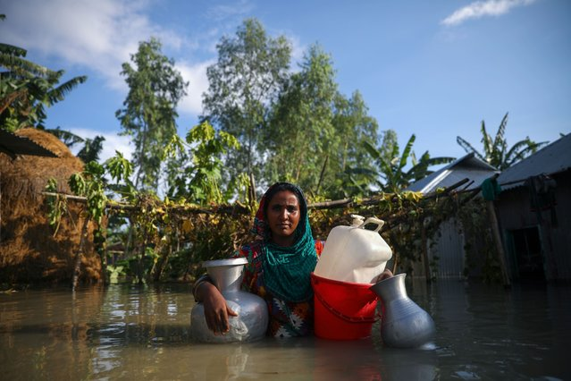 A flood-affected woman poses for a picture before collecting drinking water from a tube-well in Bogura, Bangladesh, July 17, 2020. (Photo by Mohammad Ponir Hossain/Reuters)
