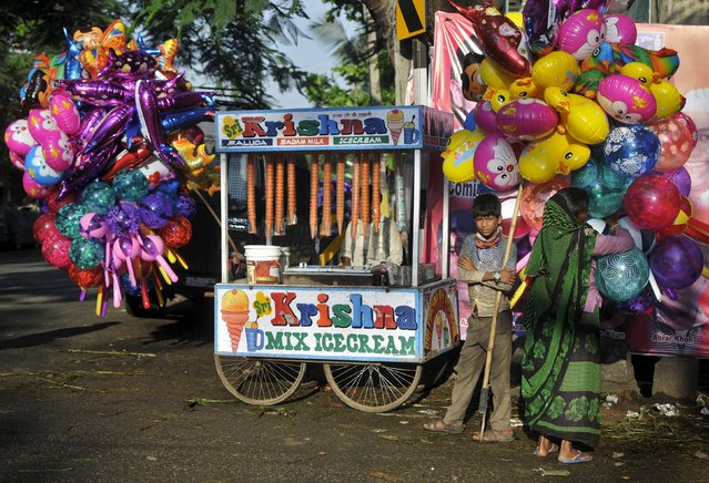 Roadside vendors selling ice-cream and balloons stand outside a public prayer ground during Eid al-Adha in Bengaluru, India, September 25, 2015. (Photo by Abhishek N. Chinnappa/Reuters)