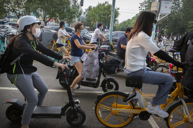 People wearing face masks to protect against the coronavirus wait at an intersection in Beijing, Wednesday, July 29, 2020. China reported more than 100 new cases of COVID-19 on Wednesday as the country continues to battle an outbreak in Xinjiang. (Photo by Mark Schiefelbein/AP Photo)