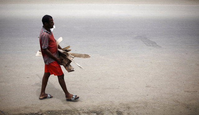 An African migrant stranded in Costa Rica carries firewood on the Inter-American Highway at the border between Costa Rica and Nicaragua, in Penas Blancas, Costa Rica, September 8, 2016. (Photo by Juan Carlos Ulate/Reuters)
