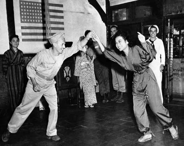 U.S. Corporal Stanley Suski, left, and Miss Tamako, a Geisha girl, whirl a bit of Jitterbug, in a bar, in Tokyo, Japan, on October 1, 1945. (Photo by AP Photo)