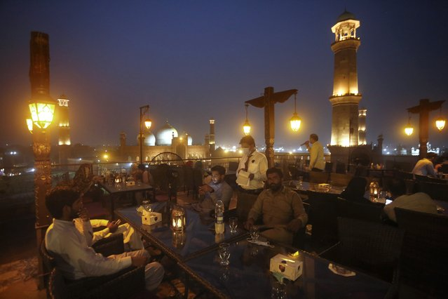 People eat at a rooftop restaurant close to the historical Badshahi Mosque, following an ease in restrictions that had been imposed to help control the coronavirus, in Lahore, Pakistan, Tuesday, August 11, 2020. Pakistan's daily virus infection rate has stayed under 1,000 for more than four weeks prompting the government to further ease restrictions for restaurants, parks, gyms and cinemas. (Photo by K.M. Chaudary/AP Photo)