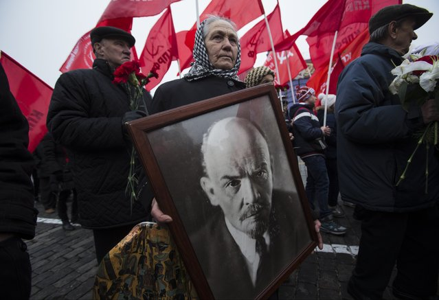 A woman carries a portrait of Lenin as she walks with the Communist Party members and supporters to place flowers at the Tomb of Soviet founder Vladimir Lenin, at Moscow's Red Square on Thursday, November 6, 2014 to mark the anniversary of the November 7, 1917 Bolshevik revolution, which is no longer a public holiday in Russia. (Photo by Pavel Golovkin/AP Photo)